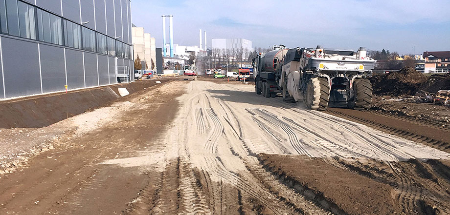 Photo: churned earth surface with numerous tire tracks; at left, an industrial hall with silver-grey panelling; at right, construction vehicles with oversized tyres