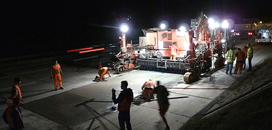 Photo: night shot of a construction site with a partially applied concrete layer, numerous workers and a large construction machine with floodlights enveloping the building site in bright light