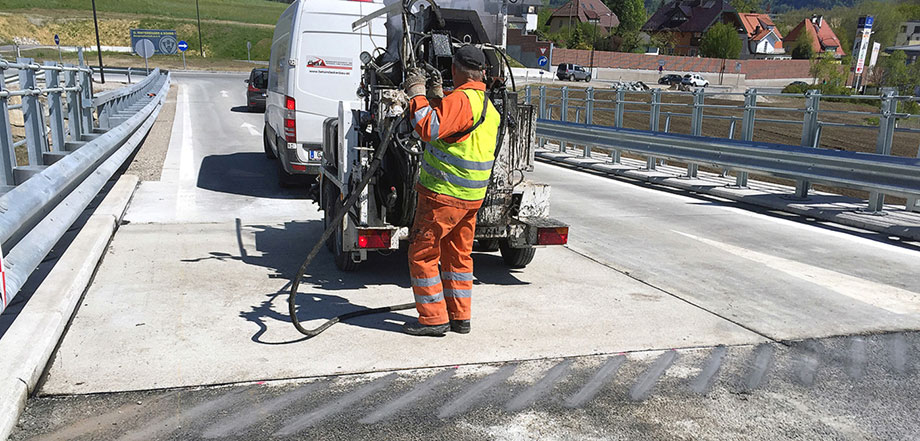 Photo: construction vehicle and a worker at a clearly visible transition between a concrete and an asphalt surface, making adjustments to a construction machine