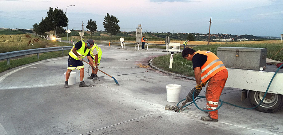 Photo: five workers at a roundabout that is closed to traffic with various tools at work